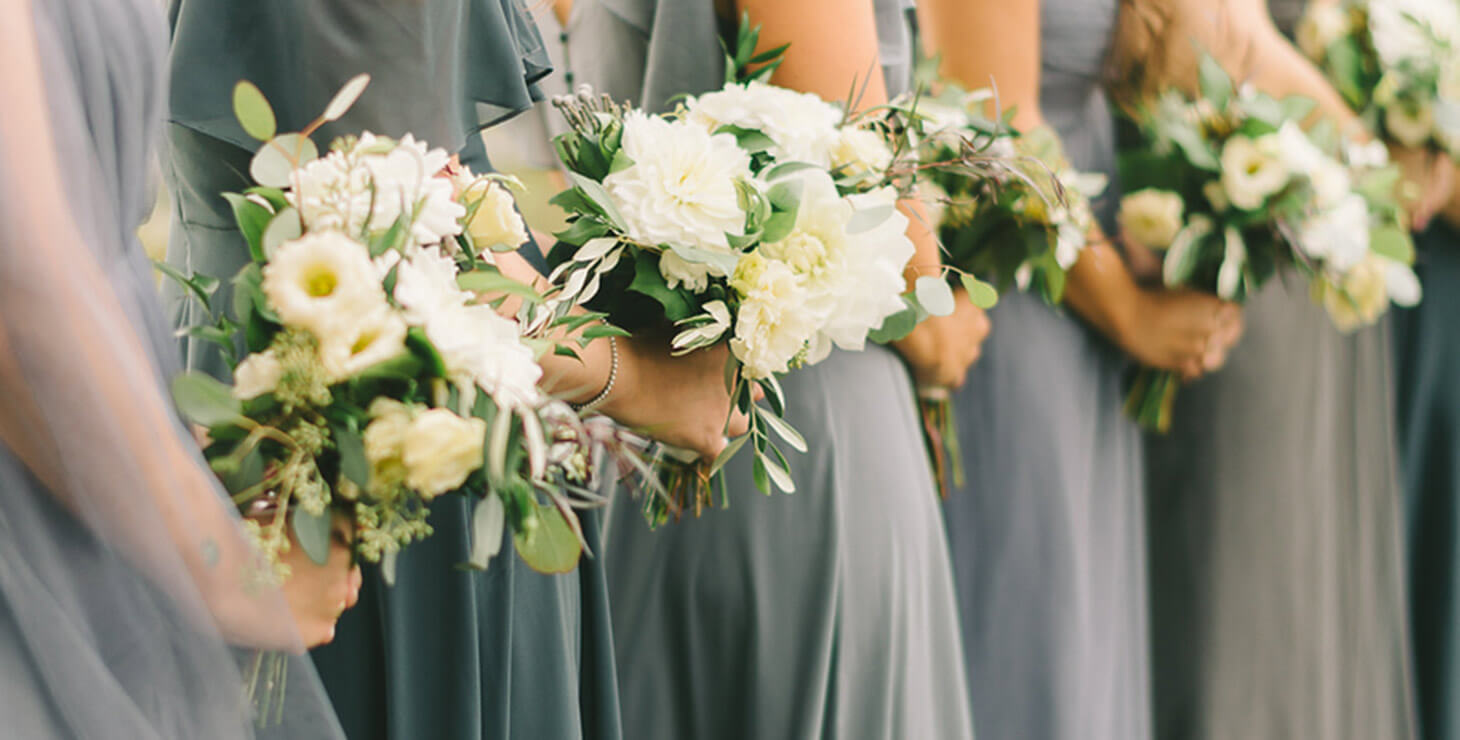 Bridesmaids in silver dresses holding white flowers at out Chesapeake Bay wedding venue