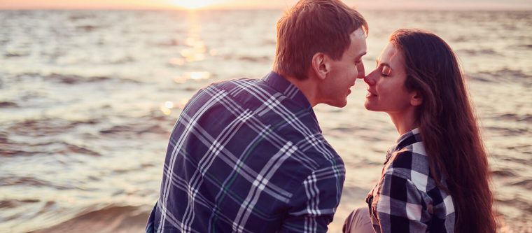 Romantic couple about to kiss by the water at sunset