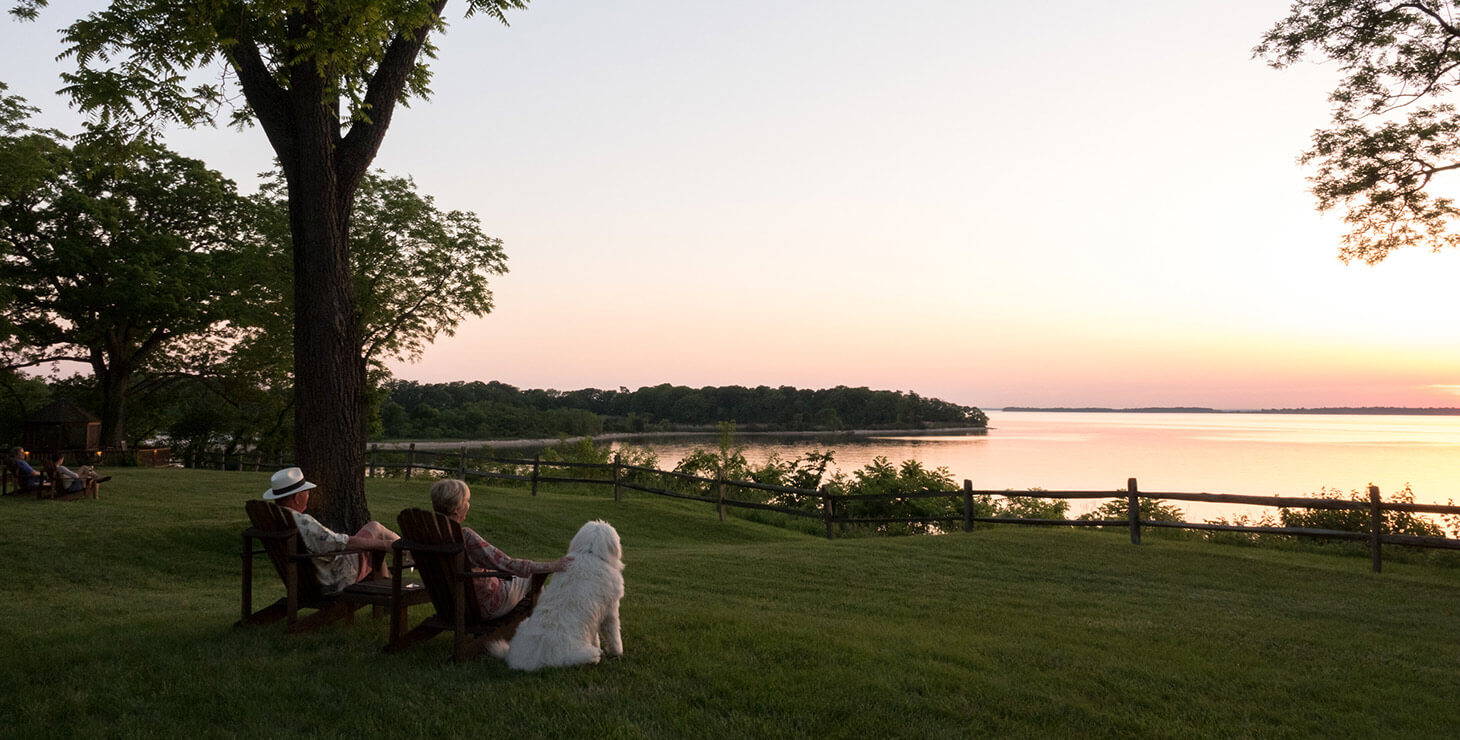 Couple and their dog watching the sunset over the water at our Chestertown B&B