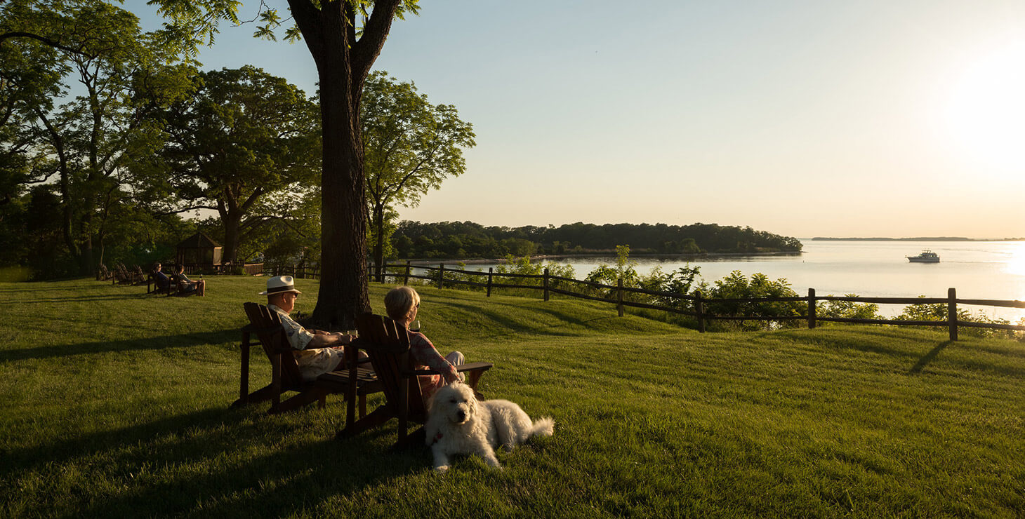 Couple with dog watching sunset over the water at our B&B on Chesapeake Bay