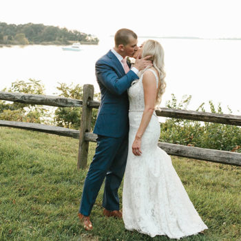 Bride and groom kiss in front of the water