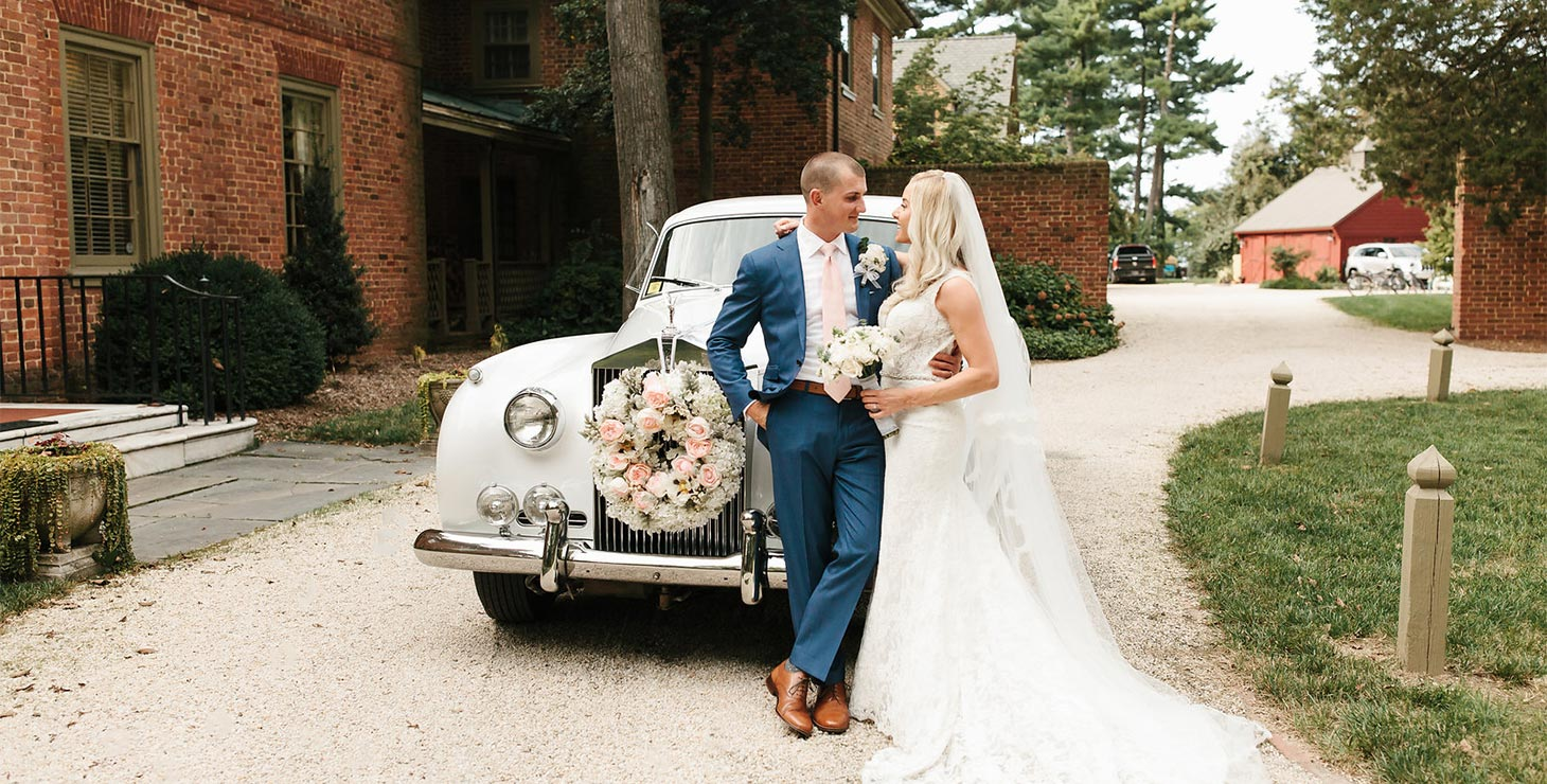 Bride and groom leaning on a classic car at our Wedding Venue on Chesapeake Bay