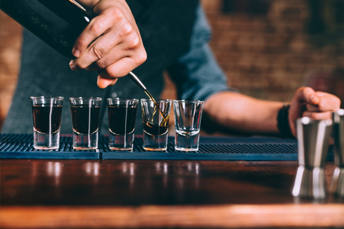 Bartender pouring whisky shots