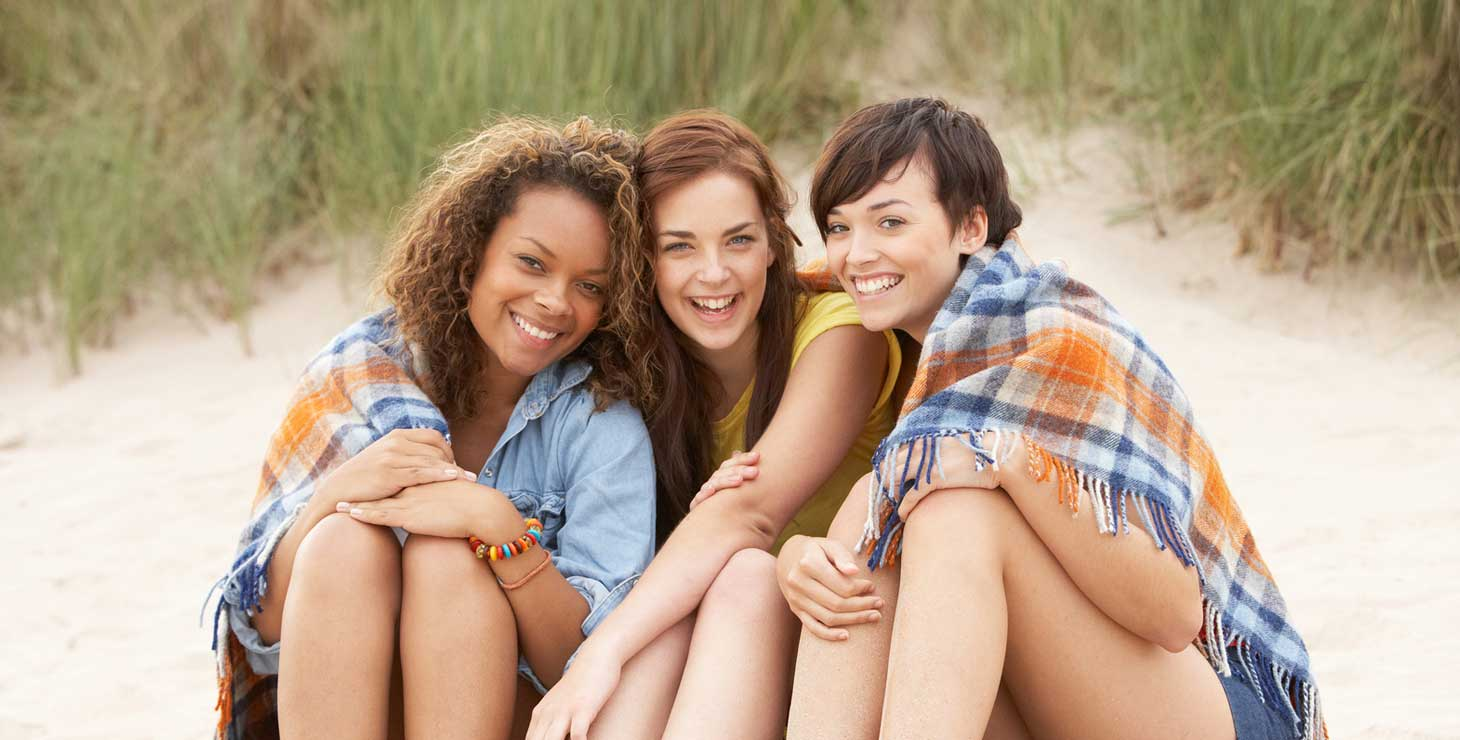 Three women wrapped in a blanket on the beach
