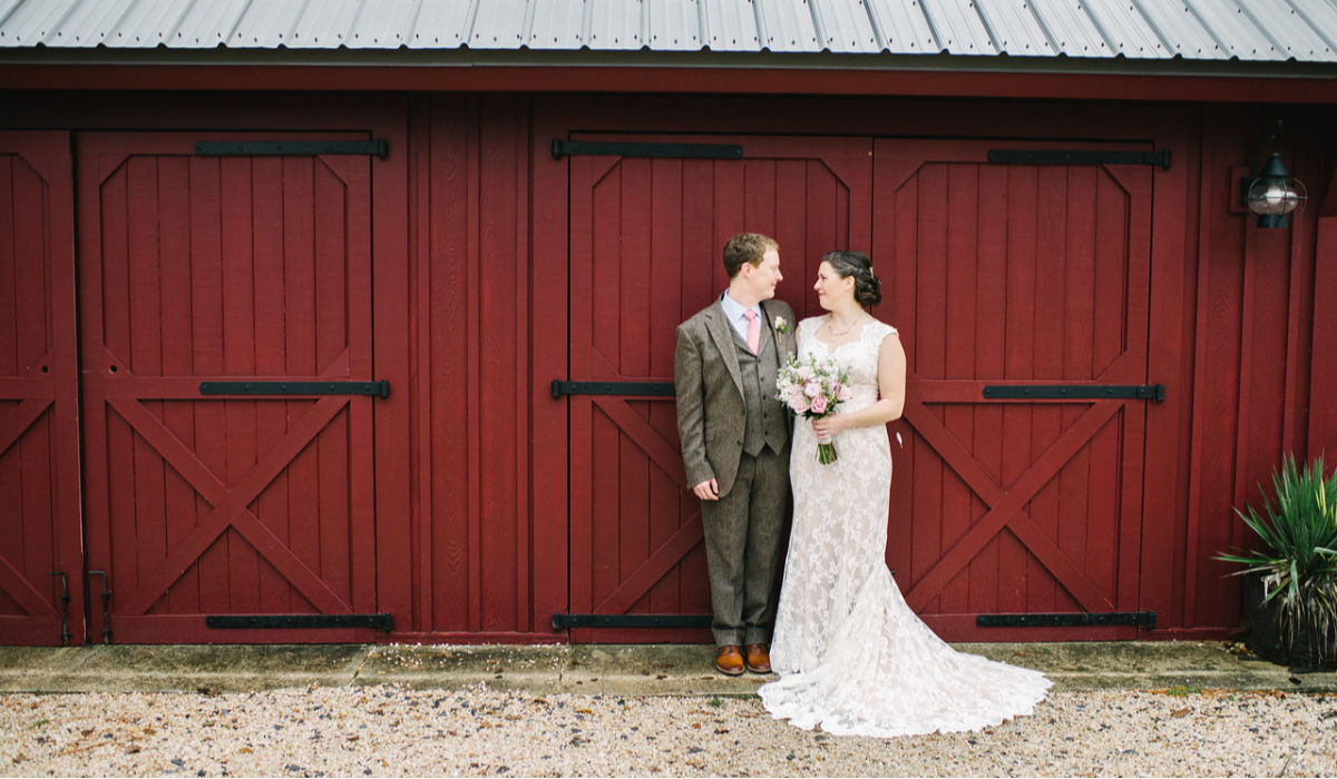 a married couple with their backs to a barn door