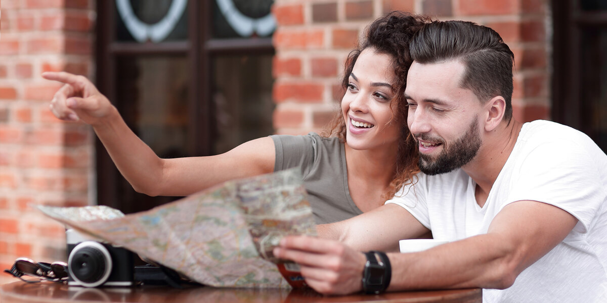 Couple at a table in front of a restaurant with map and camers