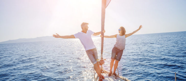 Couple on a yacht holding the mast with their arms splayed out