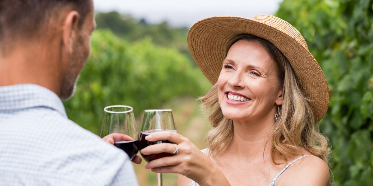 Couple in a vineyard with glasses of red wine