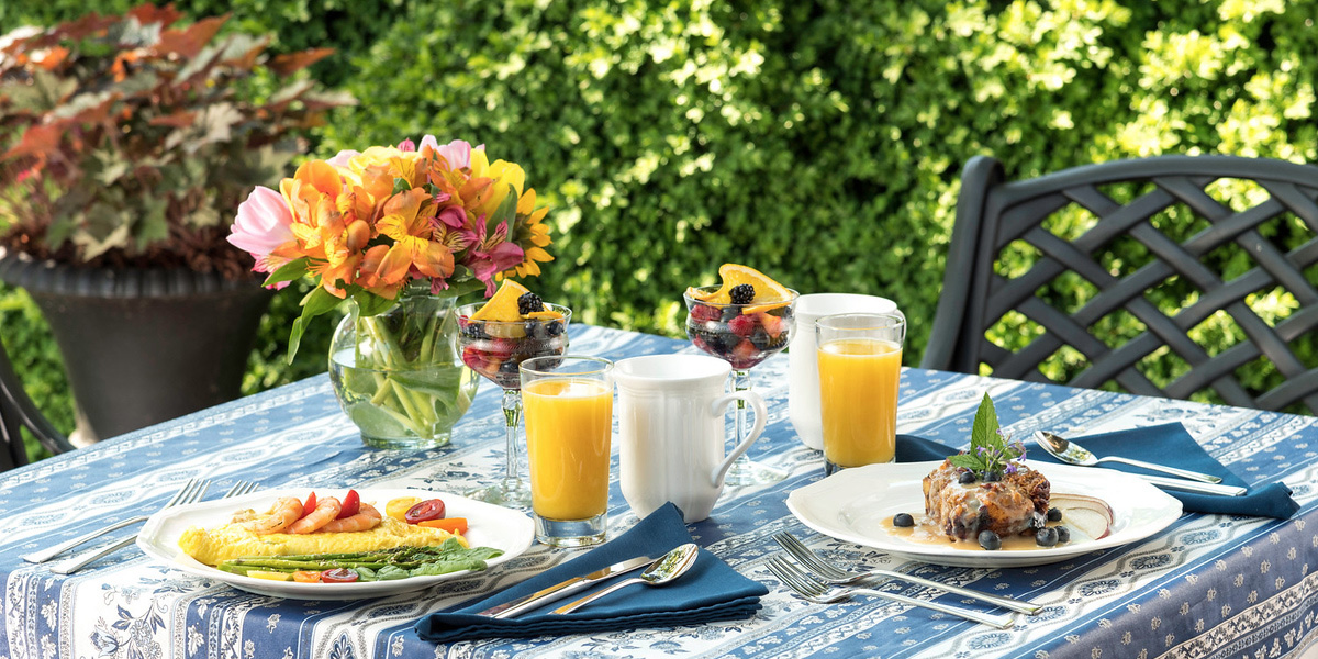Breakfast on a table outside with a blue and white tablecloth with spring flowers in a vase