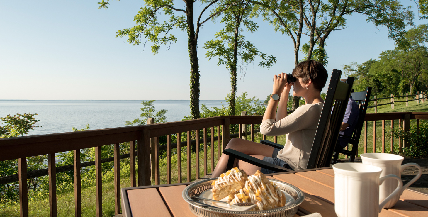a woman sitting on a deck looking through binoculars with a plate of desert on a table next to her