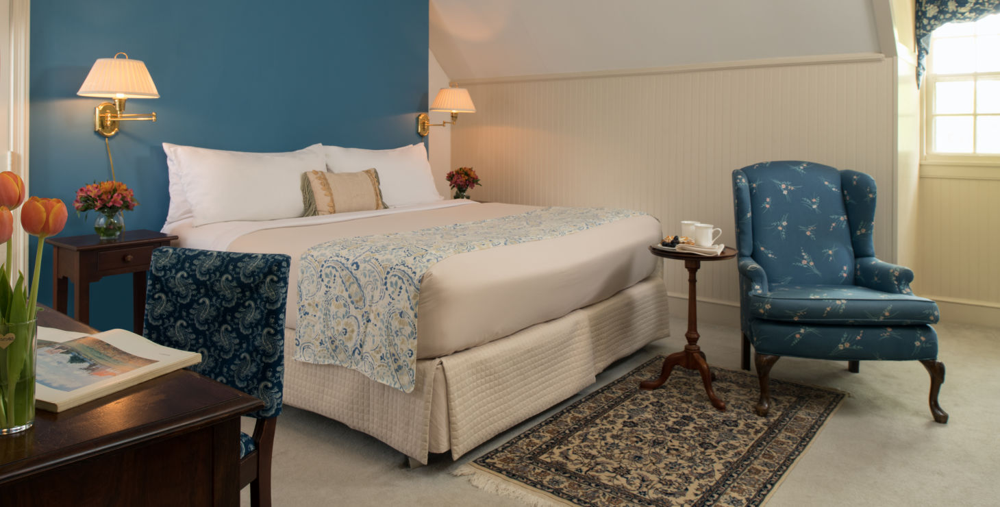 Great Oak Manor room option with bed and blue wall in the background