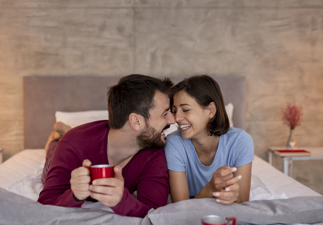 Couple enjoying coffee in bed