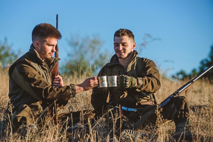 friends enjoying a hot drink while hunting