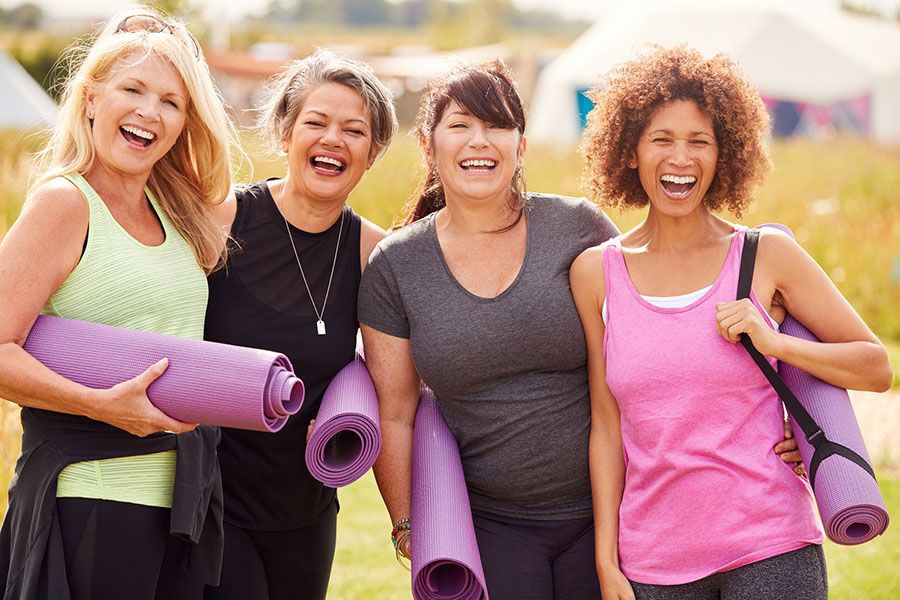 Happy women with yoga mats at our wellness retreat center in Maryland