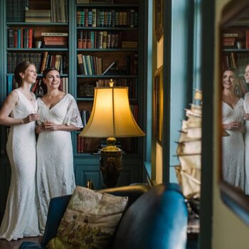 Two brides hold each other in front of the fireplace at Great Oak Manor