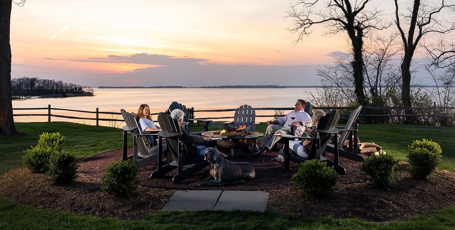 group of people sitting around the fire pit at our Maryland bed and breakfast