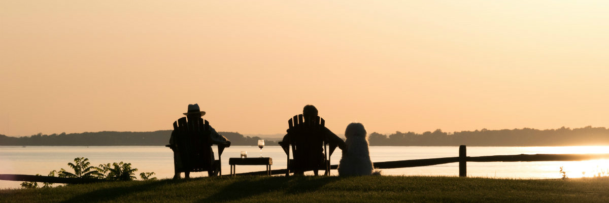 Couple and their dog enjoying the sunset views from Great Oak Manor's beach front property